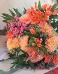 Bouquet rond pastel vif avec des dahlias, des freesias et du statice